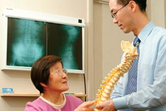 a physician showing a spinal model to an elderly woman